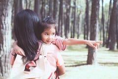 Menina asiática bonito da criança pequena que abraça sua mãe com amor Fotos de Stock
