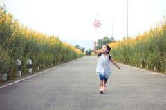 Menina asiática bonito da criança pequena que joga com turbina eólica e corrida foto de stock royalty free