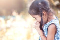 Menina asiática bonito da criança pequena que reza com dobrado sua mão foto de stock