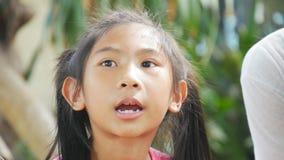 Menina asiática bonito que canta no parque exterior filme