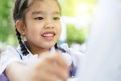 Menina asiática bonito que lê um livro na escola Imagem de Stock