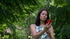 A menina asiática bonito tenta conectar a um sinal celular da rede no parque O telefone vermelho está em suas mãos filme