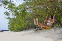 Menina asiática chinesa bonita nova que tem o divertimento no balanço da árvore da praia que aprecia o sentimento feliz livre na  imagens de stock