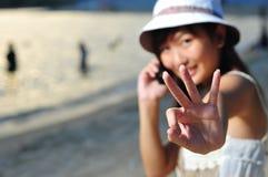 Menina asiática chinesa pequena na praia com telefone Foto de Stock