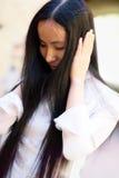 A menina asiática cobriu as orelhas com suas mãos Imagens de Stock Royalty Free