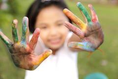 Menina com as mãos pintadas em pinturas coloridas imagens de stock