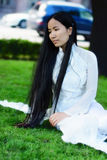 Menina asiática com assento longo dos cabelos Foto de Stock Royalty Free