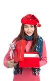 Menina asiática com a caixa de presente aberta do sorriso vermelho do chapéu do Natal Imagens de Stock