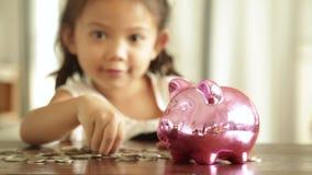 Menina asiática com dinheiro da economia, conceito do depósito video estoque