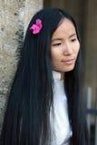 Menina asiática com a flor em seus cabelos que olham para baixo Imagens de Stock