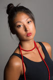 Menina asiática com grânulos vermelhos Fotos de Stock