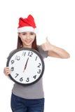 A menina asiática com o chapéu vermelho de Santa e o pulso de disparo mostram os polegares acima Fotografia de Stock
