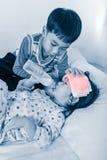 Menina asiática com o frio e a gripe que sugam acima a garrafa de leite e que relaxam Fotografia de Stock Royalty Free