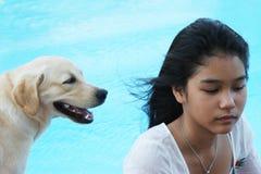 Menina asiática com seu cão de animal de estimação (o foco está na menina). Fotos de Stock