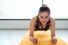 A menina asiática da aptidão da mulher faz a prancha no gym da aptidão na esteira da ioga Ele fotografia de stock