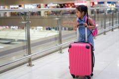 Menina asiática da criança com embarque de espera da mala de viagem da terra arrendada da trouxa no aeroporto foto de stock