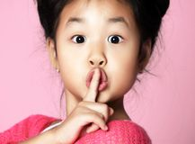 A menina asiática da criança na camiseta cor-de-rosa mostra shhh o sinal quieto no rosa foto de stock royalty free
