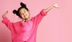 Menina asiática da criança na camiseta cor-de-rosa, nas calças brancas e em suportes engraçados dos bolos com mãos acima e sorris foto de stock