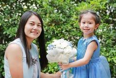 Menina asiática da criança que dá o ramalhete das flores para sua mãe no jardim imagem de stock royalty free