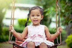 Menina asiática da criança que tem o divertimento para jogar o balanço no campo de jogos Fotos de Stock