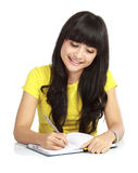 Menina asiática da faculdade que escreve um livro foto de stock royalty free