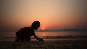 menina asiática da silhueta 4K que joga a areia na praia com grão da atmosfera do por do sol do verão e a obscuridade processada video estoque