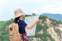 A menina asiática das crianças que guarda mapas e curso do compasso magnético backpacks a posição na montanha imagens de stock