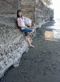 Menina asiática de Millenial que levanta ao longo da costa e contra a parede com bola, câmera, e tampão do verão Imagem de Stock Royalty Free