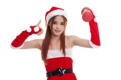 A menina asiática de Santa Claus do Natal manuseia acima com peso vermelho Foto de Stock