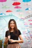 Menina asiática de sorriso com guarda-chuvas Imagens de Stock