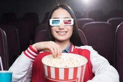 menina asiática de sorriso nos vidros 3d com a cesta grande do filme de observação da pipoca Foto de Stock Royalty Free