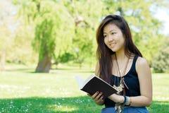 Menina asiática de sorriso que lê um livro Imagem de Stock Royalty Free