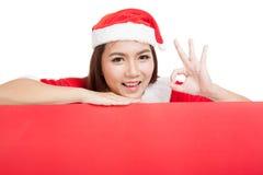 A menina asiática do Natal com roupa de Santa Claus mostra ESTÁ BEM com placa Imagem de Stock