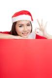A menina asiática do Natal com roupa de Santa Claus mostra ESTÁ BEM com placa Fotografia de Stock Royalty Free