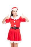 A menina asiática do Natal com roupa de Santa Claus mostra os polegares acima fotografia de stock
