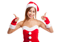 A menina asiática do Natal com roupa de Santa Claus mostra os polegares acima Fotografia de Stock Royalty Free