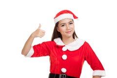 A menina asiática do Natal com Santa Claus veste os polegares acima Foto de Stock Royalty Free