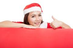 A menina asiática do Natal com Santa Claus veste os polegares acima com bla Imagem de Stock