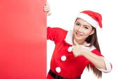 A menina asiática do Natal com Santa Claus veste os polegares acima com bla Foto de Stock Royalty Free
