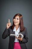 A menina asiática do negócio leu um livro vem acima com ideia Imagens de Stock Royalty Free