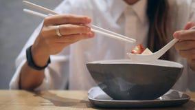 Menina asiática do turista que come com hashis Tom Yam Noodle Soup tradicional no restaurante 4K vídeos de arquivo