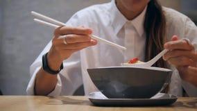 Menina asiática do turista que come com hashis Tom Yam Noodle Soup tradicional no restaurante 4K filme
