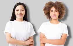 Menina asiática e afro-americano na camisa vazia do molde t isolada no fundo cinzento Mulheres no tshirt com espaço e zombaria da fotografia de stock royalty free