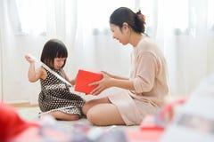 Menina asiática e sua mãe que desempacotam um toget vermelho da caixa de presente imagem de stock royalty free
