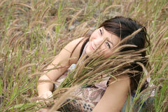 Menina asiática entre a grama Fotografia de Stock