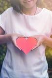 A menina asiática está tomando um papel do coração no fundo da planta fotos de stock royalty free