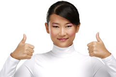 Menina asiática feliz bonita que mostra os polegares acima foto de stock