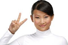 Menina asiática feliz bonita que mostra a vitória o sinal positivo foto de stock royalty free