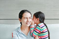 Menina asiática feliz da criança que compartilha de um segredo a sua mamã na sala de visitas em casa Bisbolhetice de sussurro da  fotos de stock royalty free