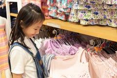 A menina asiática feliz está escolhendo a roupa na loja da alameda ou de roupa, s imagem de stock